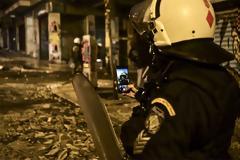 Απίστευτη φωτογραφία από το Γαλλικό Πρακτορείο Ειδήσεων: Η selfie αστυνομικού των ΜΑΤ στα αποκαΐδια των επεισοδίων!