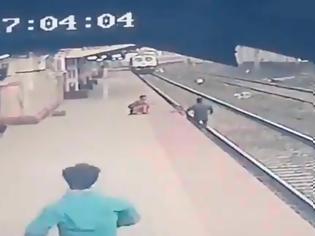 Φωτογραφία για Ινδία : Σιδηροδρομικός υπάλληλος πέφτει στις ράγες για να σώσει παιδί από διερχόμενο τρένο. Βίντεο.
